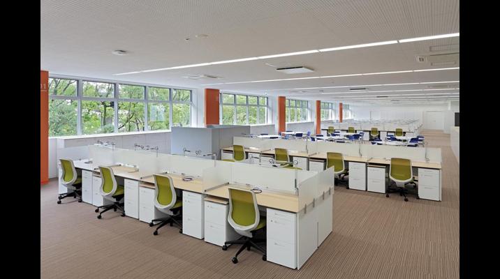視界を遮るもののないオープンで一体感のある「執務空間」。窓からは緑が全面に広がります。デスクには、森をイメージする木柄の天板を採用しました。