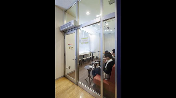 喫煙室の煙が外に流れないよう、入口にはエアカーテンを設置。また、汚れを目立たせない為、濃い目の色合いで全体をデザイン。