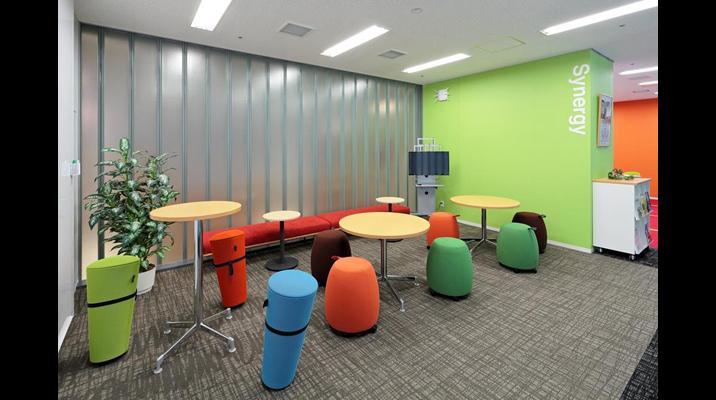 「シナジー」エリア。動きのあるスツールを配置した、数人単位で、柔軟にミーティングできるスペース。ポップな色使いで、社員が気軽な交流によってシナジー効果を創出することを狙いとしています。