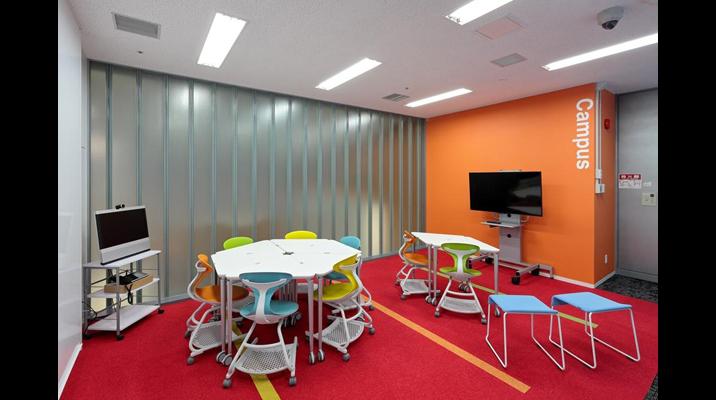 「キャンパス」エリア。三角形のテーブルを自由に組み合わせることで多様な会議・講習会が開催可能なスペース。TV会議システムを介した海外サイトとのミーティングも可能。活気ある空間にするため、全体的にビタミンカラーを採用しました。