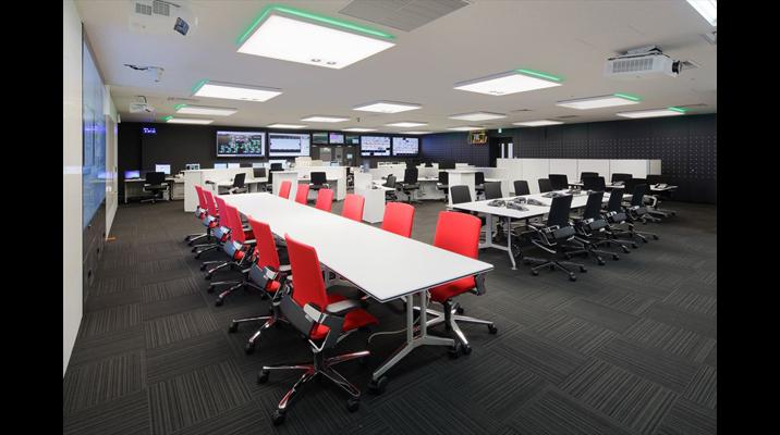 座席はフリーアドレスで運用。手前の赤い椅子の席は消防隊活動スペースを確保するためキャスターつきのテーブルを使用しています。