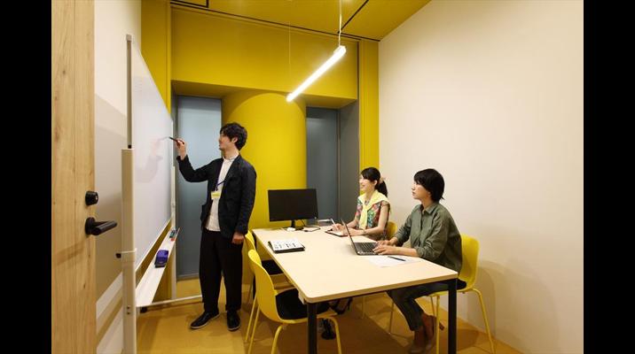 印刷に用いられるカラーモデル「CMYK」で彩られたボックスの中は、ディスプレイとホワイトボードを完備したミーティングルーム。