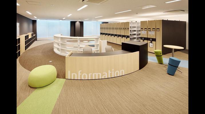 ライブラリーエリアはコンシェルジュも常駐。無機質になりがちな移動書架は、木調の仕上げ材を用いて落ち着いたインテリアになじませています。