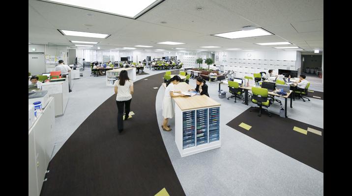 オペレーション改革・IT企画部門の執務エリア。キャスター付のテーブルを使用したフリーアドレスオフィス。「ベンチシート」や間仕切りのある「集中デスク」など、働き手は自立的に働く場所を選んで仕事することができます。