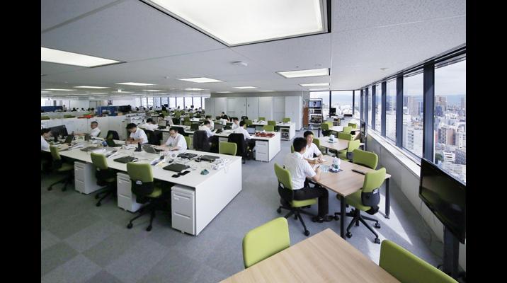 大阪本社の標準フロアの執務エリア。従来、役職者が占めていた窓際は、ひな壇を廃止しミーティングスペースとして利用しています。