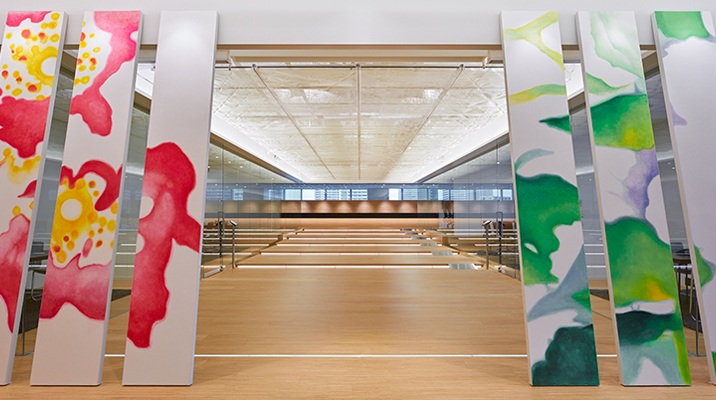 玄関口には企業のエンブレムとして暖簾が掲げられる。壁画工房さ組 佐倉康之氏によるアート。